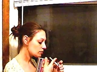 Brown-haired Housewife With A Hair Knot Smoking At The Window