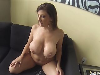 Lusty Housewife With Monster Tits Leans Over Naked On A Black Couch...